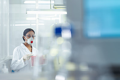 Female scientist in isolation environment wearing masks, working in research laboratory. - p429m2200753 by Monty Rakusen