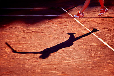 Shadow of the girl playing tennis at clay court - p1025m788489f by Mujo Korach