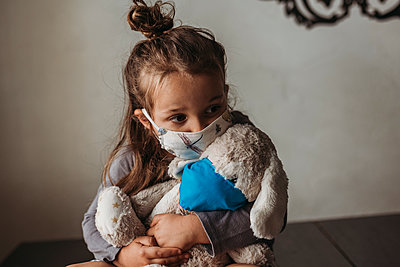 Close up of young girl with mask on kissing masked stuffed animal - p1166m2207792 by Cavan Images