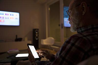 Senior man using smart TV apps on smart phone in dark living room - p1192m1517022 by Hero Images