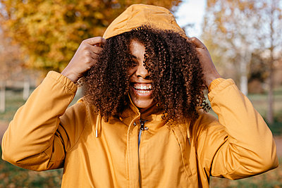 Cheerful Afro woman holding jacket hood in park during autumn  - p300m2267522 by Tania Cervián