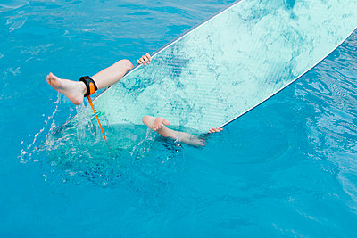 Boy playing with surfboard in swimming pool - p300m2281388 by Lightsy Studio