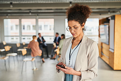 Female entrepreneur using mobile phone with colleagues in background at office - p300m2281426 by Annika List