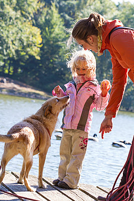 Mother and daughter and their begging dog standing on a boardwalk - p300m978800f by Jana Fernow