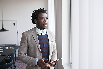 Man holding digital tablet, looking through window - p312m1338781 by Viktor Holm