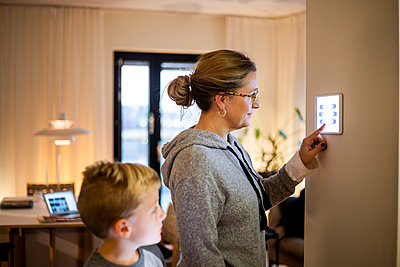 Son looking at mother using digital tablet mounted on wall at smart home - p426m2195380 by Maskot