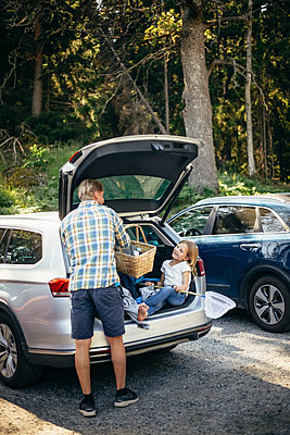 Rear view of father standing with picnic basket while daughter sitting in car trunk - p426m2212168 by Maskot