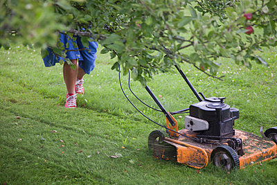 Woman In Blue Dress Cuts The Grass With A Lawn Mower Engine (Kvinna i blå klänning klipper gräset med en motorgräsklippare) - p847m673328 by Johan Strindberg