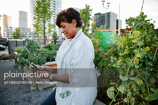 Woman using smart phone in urban community garden - p1192m2130140 by Hero Images