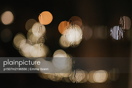 Lights in the darkness behind windowpane - p1507m2196556 by Emma Grann