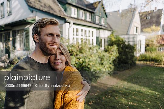 Smiling couple embracing in garden of their home - p300m2166647 von Kniel Synnatzschke