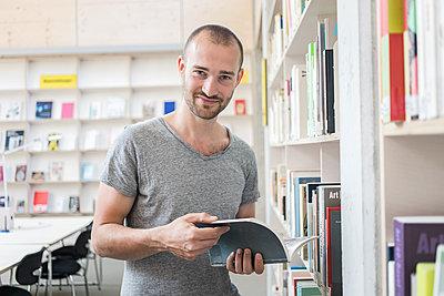 Student in Bibliothek liest ein Fachbuch - p1284m1452123 von Ritzmann