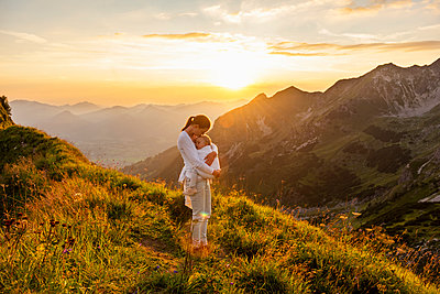 Germany, Bavaria, Oberstdorf, mother holding little daughter on a hike in the mountains at sunset - p300m2028808 von Daniel Ingold