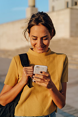 Smiling young woman looking at cell phone outdoors - p300m2058587 by VITTA GALLERY