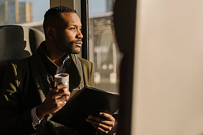 Portrait of stylish businessman with reusable cup and documents inside a train - p300m2154622 by Hernandez and Sorokina
