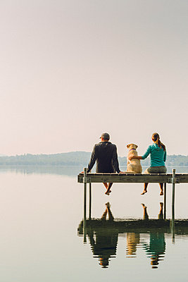 Woman, dog and man relaxing on the end of long lake dock. - p343m1173357 by Corey Hendrickson
