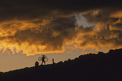 Mountain Biker Carries Bike Up Rocky Slope, Sunset Clouds Behind, Whistler, Bc Canada - p442m837463f by Leanna Rathkelly