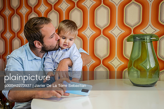 Caring father kissing son while taking selfie at table - p300m2273937 by Javier De La Torre Sebastian