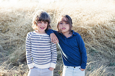 Portrait of brothers standing against heap of hay at field - p1166m1489569 by Cavan Images