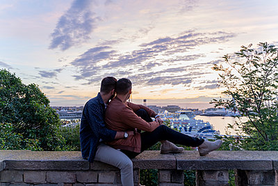 Affectionate gay couple on lookout above the city with view to the port, Barcelona, Spain - p300m2155130 by VITTA GALLERY