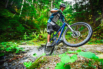 Mountain biker rides passes a small creek in Chamonix, France. - p343m1090326 by Elias Kunosson