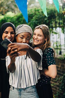 Happy multi-ethnic female friends taking selfie through mobile phone in backyard - p426m2046242 by Maskot