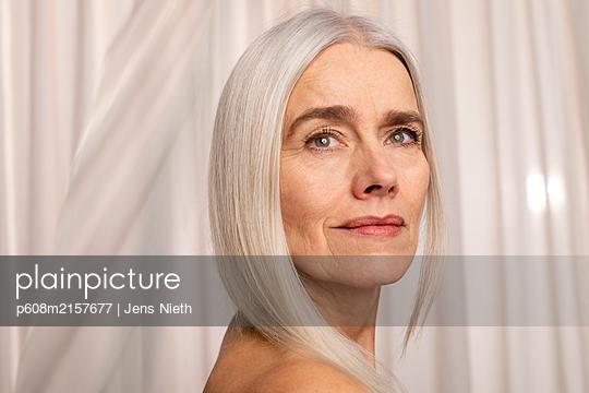 Portrait of elderly woman with long grey hair - p608m2157677 by Jens Nieth