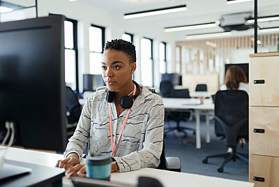 Businesswoman working at computer in open plan office - p1023m2261542 by Paul Bradbury