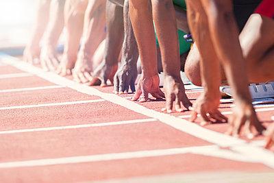 Runners poised at starting blocks on track - p1023m946888f by Tom Merton