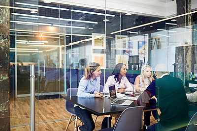 Business people at conference table during meeting seen through glass doors in office - p1166m1523254 by Cavan Images