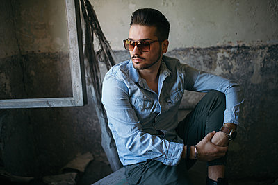 Portrait of a handsome young man with sunglasses in old house. - p1166m2152010 by Cavan Images