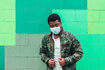 Afro American black boy on green wall background. Dressed in military jacket and face mask. - p1166m2254951 by Cavan Images