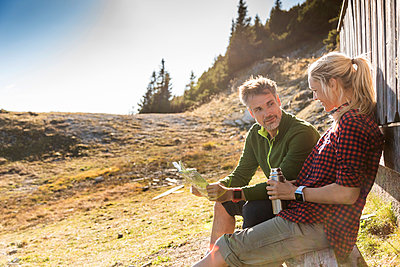 Hiking couple sitting in front of mountain hut, taking a break, holding map - p300m2069916 by Uwe Umstätter