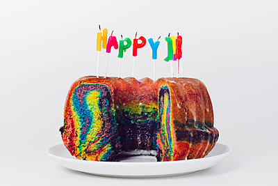 Close-up of birthday candles on rainbow cake in plate against white background - p301m1406353 by Norman Posselt