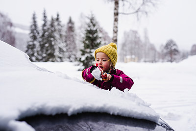 Girl brushing snow from car - p312m2145537 by Anna Johnsson