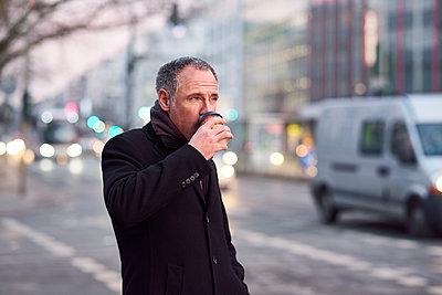 Mann trinkt Kaffee in der Stadt - p890m1217697 von Mielek
