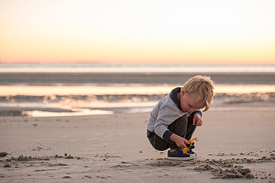 Boy playing with toy while crouching at beach against sky during sunset - p1166m1566822 by Cavan Social