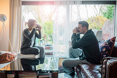 Couple in living room at home taking pictures of each other - p300m1536270 by Robijn Page