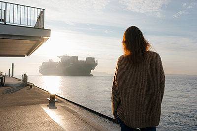 Germany, Hamburg, woman standing on pier at the Elbe shore with container ship in background - p300m2080571 by Joseffson