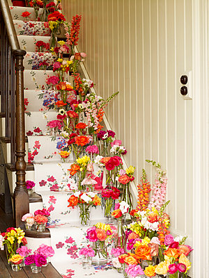 Vases of flowers on staircase with floral wallpaper  - p349m2167680 by Polly Wreford