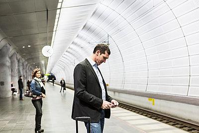 Businessman using mobile phone at railroad station - p426m1085307f by Kentaroo Tryman
