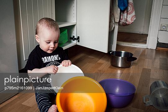 Baby boy creates choas in kitchen after clearing out kitchen cupboard - p795m2161099 by JanJasperKlein