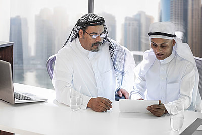 Two Middle Eastern businessmen sitting office, looking at digital tablet - p300m1120673f by zerocreatives