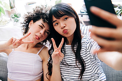 Female friends showing peace sign while taking selfie through smart phone at home - p300m2293300 by Angel Santana Garcia