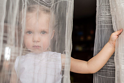 Girl staring behind translucent curtains - p301m799522f by Vladimir Godnik