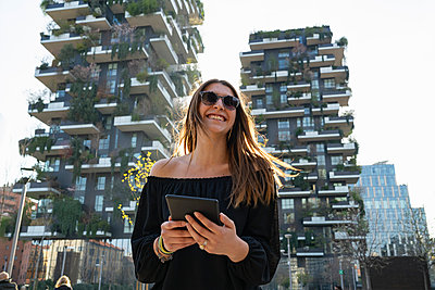 Young woman using digital tablet in city, Milano, Lombardia, Italy - p429m2127790 by Francesco Buttitta
