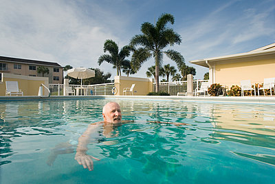 Senior man in a swimming pool, Florida, USA - p442m2154648 by Mark Hunt