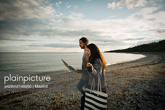 Woman walking with man using laptop on sea shore at beach against sky - p426m2149250 by Maskot