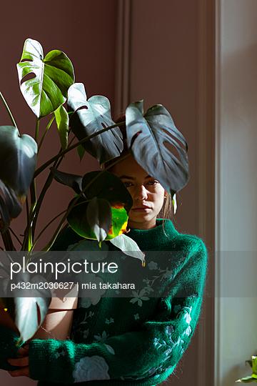 Junge Frau hält Topfpflanze in der Hand - p432m2030627 von mia takahara
