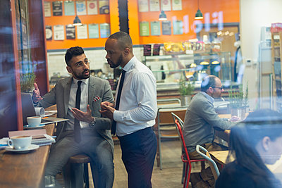Businessmen using laptop, working in cafe - p1023m2017063 by Paul Bradbury